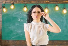 Woman with long hair in white blouse stands in classroom. Strict teacher concept. Lady strict teacher on calm face. Stands in front of chalkboard. desire stock images