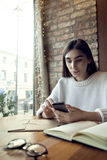 Woman with long hair work in cafe with phone near window. Woman with long hair work in cafe with phone window Royalty Free Stock Images