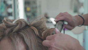 Woman with Long Hairs, hairdresser`s hands close up, Barbershop. Stylist. Hair stylist making curls on customer hair using electric curler. Beauty saloon. Woman stock video footage