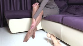 Woman with long in high heels. A tired woman takes off her high-heeled shoes and massages her feet stock video