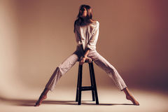 Woman with long legs sitting on chair. In studio at sunset Stock Photo
