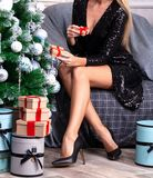 Woman with long legs sitting by the Christmas tree stock images