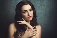 Woman with long nails. Beautiful brunette woman with curly hair, bright make up orange lips smoky eyes, skin, shoulders, face. Very long colorful nails new shape Stock Photos