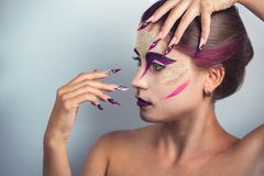 Woman long nails. Pretty Girl woman painter bright colorful ink streams, all face Painted gouache watercolor acrylic oil paints. Creative makeup new conceptual stock image