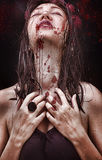 Woman with a long neck, beautiful shoulders, wet hair, tragic expression on his face and a drop of blood royalty free stock photography