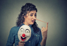 Woman with long nose and clown mask. Liar concept Royalty Free Stock Image