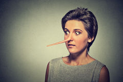 Woman with long nose  on grey wall background. Liar concept Royalty Free Stock Photos
