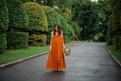 Woman in long orange dress standing on the road with bouquet of flowers Stock Photo