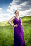 Woman in long purple dress posing on meadow at sunny day Stock Image