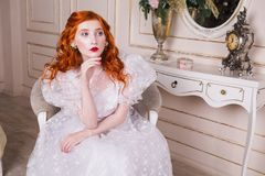 Beautiful girl with red hair. Woman with long red curly hair in a white vintage wedding dress with white pearl earrings on her ears. Red-haired girl with pale Stock Image