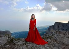Woman in long red dress on the edge of a cliff in the mountains. Peak of Ai-Petri mountain. Beautiful woman in long red dress on the edge of a cliff in the Stock Photo