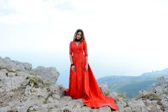 Woman in long red dress on the edge of a cliff in the mountains. Peak of Ai-Petri mountain. Beautiful woman in long red dress staying on the edge of a cliff in Royalty Free Stock Photos