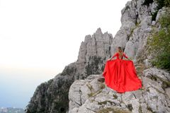 Woman in long red dress on the edge of a cliff in the mountains. Peak of Ai-Petri mountain. Woman in long red dress on the edge of a cliff in the mountains Royalty Free Stock Photography