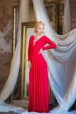 Woman in long red dress. Luxury interior Royalty Free Stock Photos