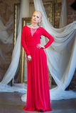 Woman in long red dress. Luxury interior Stock Photos