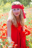 Woman in long red dress among poppy field Royalty Free Stock Image