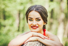 Woman in long red dress walking in the forest Stock Images