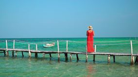 The woman in a long red dress. The young woman in a red dress costs on a pier and looks afar. Sunny day on the island. On this video you can see as the woman in stock video footage