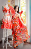 Woman in Long Red Floral Dress in Fashion Store. Girl in a clothes shop in a maxi summer dress Stock Photo
