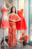 Woman in Long Red Floral Dress in Fashion Store. Girl in a clothes shop in a maxi summer dress Stock Photography