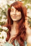Woman With Quirky Grin In Spring Blossom. Woman with long red hair in Spring blossom royalty free stock photography