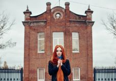 Woman with long red hair walks in autumn on the street. Mysterious dreamy look and the image of the girl. Redhead woman walking. In the autumn the city. Cold Royalty Free Stock Photo