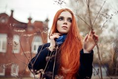 Woman with long red hair walks in autumn on the street. Mysterious dreamy look and the image of the girl. Redhead woman walking Royalty Free Stock Photos