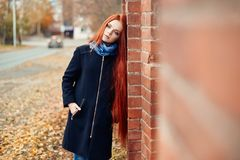Woman with long red hair walks in autumn on the street. Mysterious dreamy look and the image of the girl. Redhead woman walking. In the autumn the city. Cold Stock Images