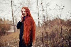 Woman with long red hair walks in autumn on the street. Mysterious dreamy look and the image of the girl. Redhead woman walking. In the autumn the city. Cold Stock Photo