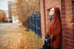 Woman with long red hair walks in autumn on the street. Mysterious dreamy look and the image of the girl. Redhead woman walking Stock Photos