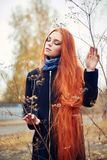 Woman with long red hair walks in autumn on the street. Mysterious dreamy look and the image of the girl. Redhead woman walking. In the autumn the city. Cold Stock Image