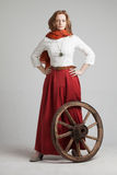 Woman in long red skirt  standing near wheel of Stock Photography