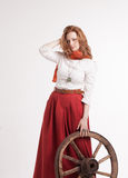 Woman in long red skirt  standing near wheel of Stock Image