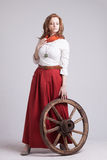 Woman in long red skirt  standing near wheel of Royalty Free Stock Photos