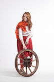 Woman in long red skirt  standing near wheel of Royalty Free Stock Photography