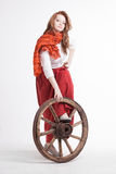 Woman in long red skirt  standing near wheel of Stock Photo