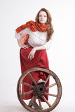 Woman in long red skirt  standing near wheel of Royalty Free Stock Image