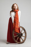 Woman in long red skirt  standing near wheel of Royalty Free Stock Photo