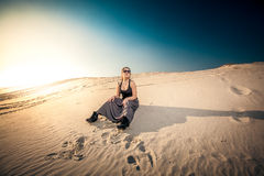 Woman in long skirt sitting on sand dune Royalty Free Stock Photo