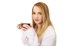 Woman in long sleeve shirt drinking coffee. Stock Image