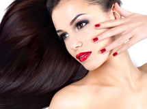Woman with long straight hairs and elegance nails. Beautiful woman with long brown straight hairs and elegance red nails royalty free stock photography