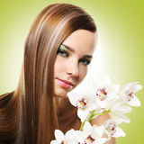 Woman with long straight hairs and flowers Stock Photography