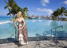 The woman in a long sundress before infiniti pool, overlooking the sea Royalty Free Stock Image