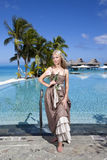 The woman in a long sundress before infiniti pool, overlooking the sea Royalty Free Stock Photography