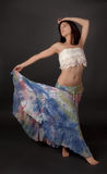 Woman in Long Tie Dye Skirt. An image of a young woman wearing a long skirt, in a graceful dance-like pose Stock Image