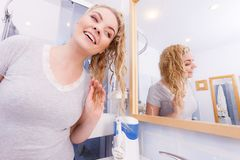 Woman looking at herself in bathroom mirror. Woman with long wet curly hair in bathroom looking in mirror. Blonde girl taking care refreshing her hairstyle in royalty free stock image