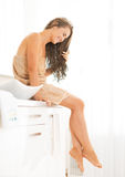 Woman with long wet hair sitting in bathroom Stock Photos