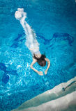 Woman in long white dress diving underwater at swimming pool Stock Image