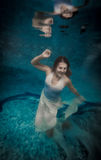 Woman in long white dress drowning at deep swimming pool Royalty Free Stock Image