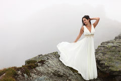 Woman in long white dress on mountain top. Beautiful bride in white dress standing on the edge of mountain top surrounded by fog Stock Photography